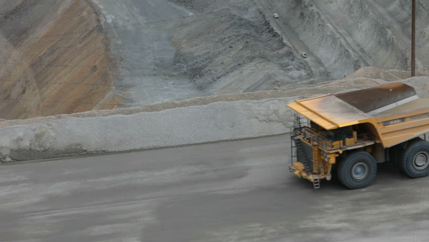 Mine dump truck in Kennecott Copper Mine central Utah. Open pit. Worlds largest open pit copper mine.  Ophir Mountains Salt Lake City. Trucks full of tons of rock and minerals driving slow.
