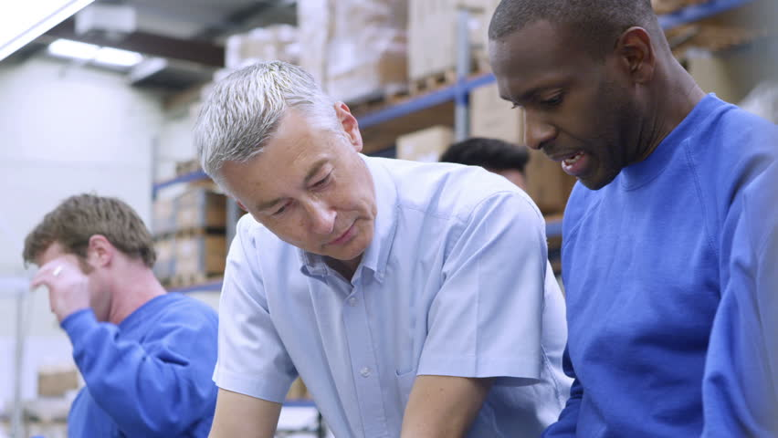 Cheerful black factory worker is discussing his work with his line manager or supervisor.