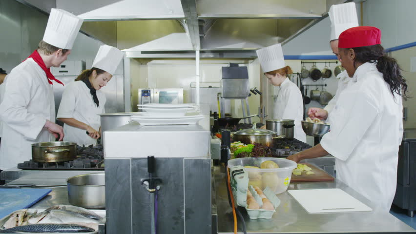 Team Of Professional Chefs Preparing And Cooking Food In A Commercial  Kitchen.   HD Stock