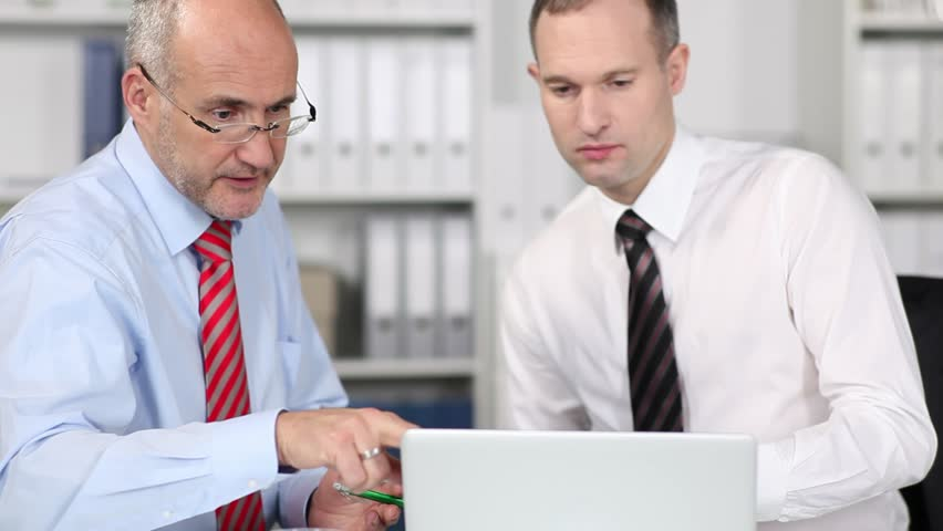 Two businessman seated at a table in an office looking at a laptop discussing information on the screen, cropped view