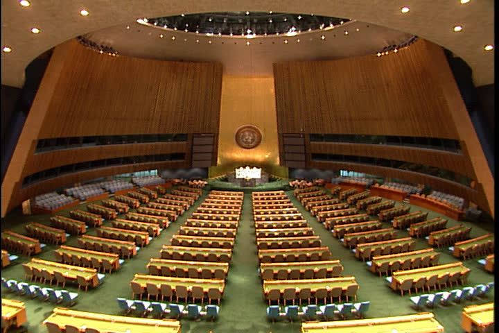 NEW YORK CITY - FEBRUARY 11, 1999: Beautiful wide angle fisheye lens shot of the United Nations General Assembly hall: speakers podium in the background: rows of seats in the foreground.
