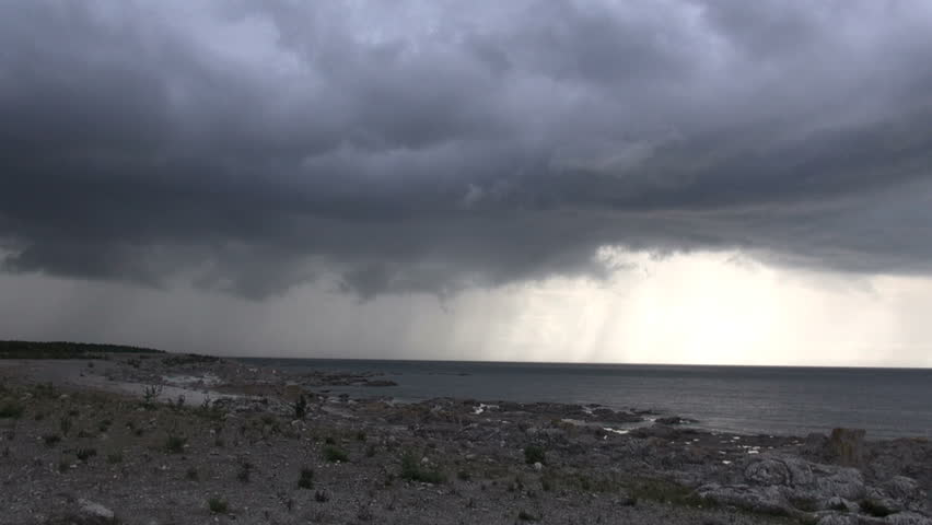 Heavy thunder storm clouds rolling in over the ocean with a limestone rock formation in the foreground