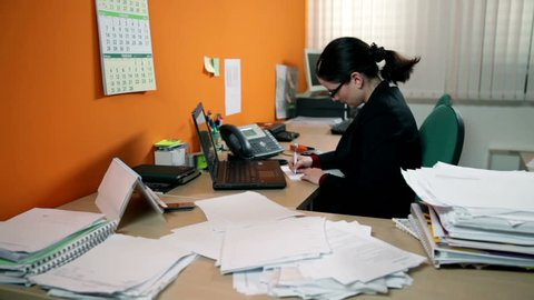 Business woman having a lot of work in office, making phone call