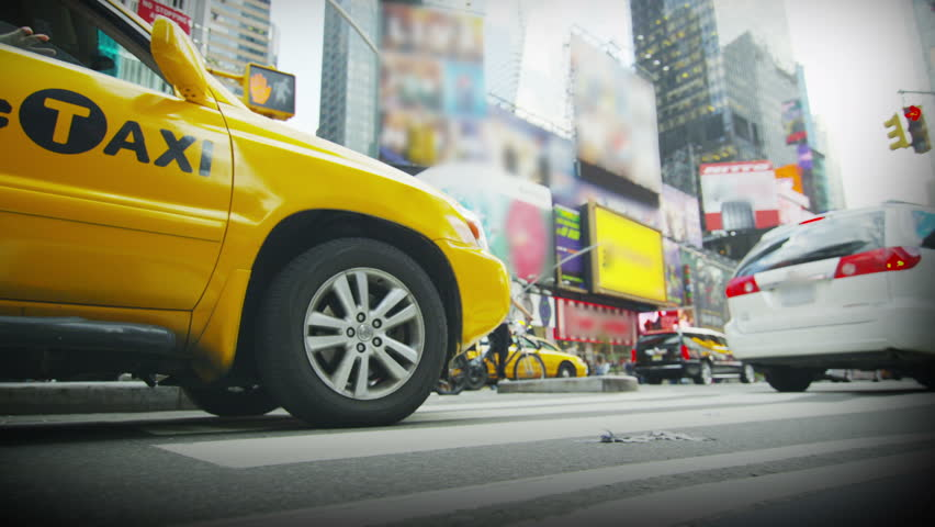 An easily recognizable Yellow taxi waiting in traffic in New York City.