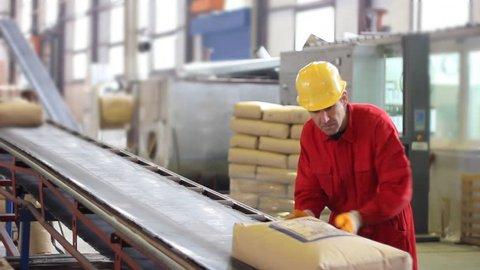 Worker controls sacks of sugar on the conveyor belt in a sugar factory