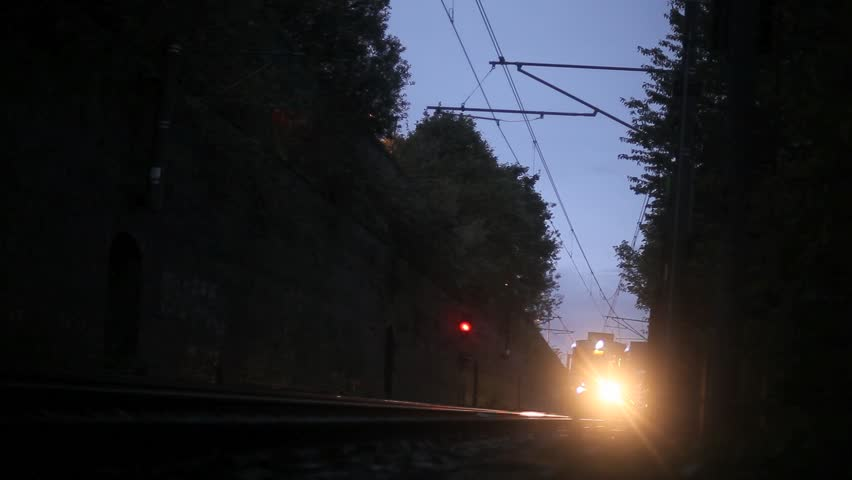 A train/tram speeds onwards towards camera in late evening