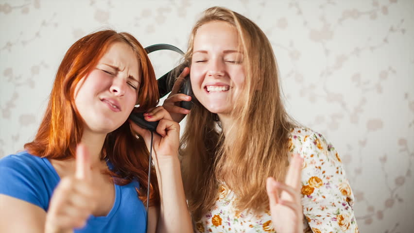 The girls listen to music, The young women like to listen to music through headphones