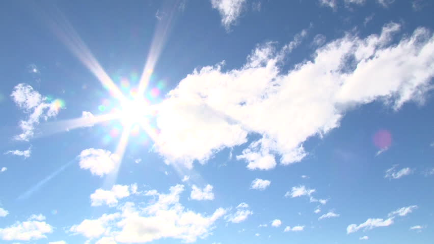 Blue sky day with bright sun shining bright with solar flare, slow time lapse.