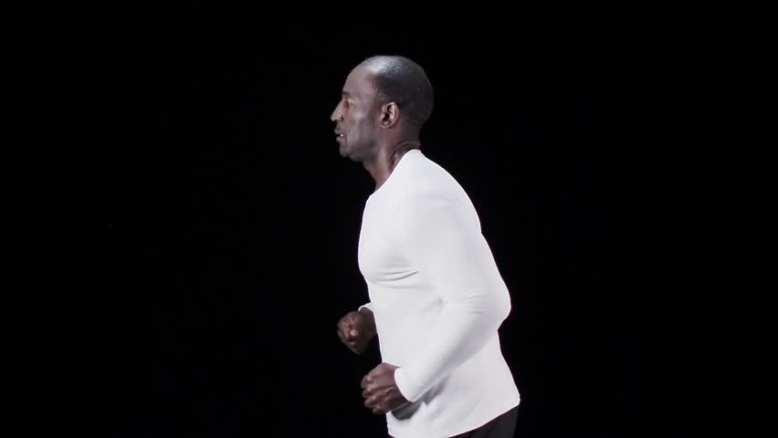 Slow motion sports man running on black background