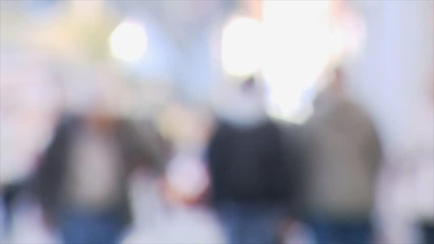 Defocused, blurry people walking in the city