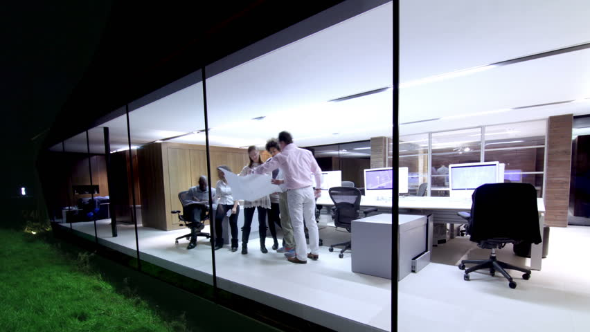 Time lapse of contemporary small creative business working late through the night.  Casual young people in architecture company.