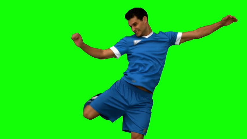 Football player kicking a football on green screen in slow motion