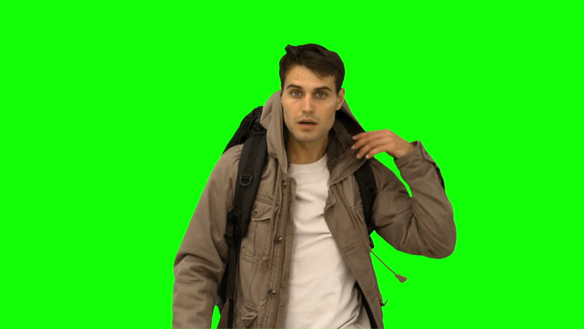 Handsome man walking towards the camera on green screen in slow motion