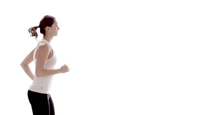 Young healthy woman running against a white background. Slow motion.