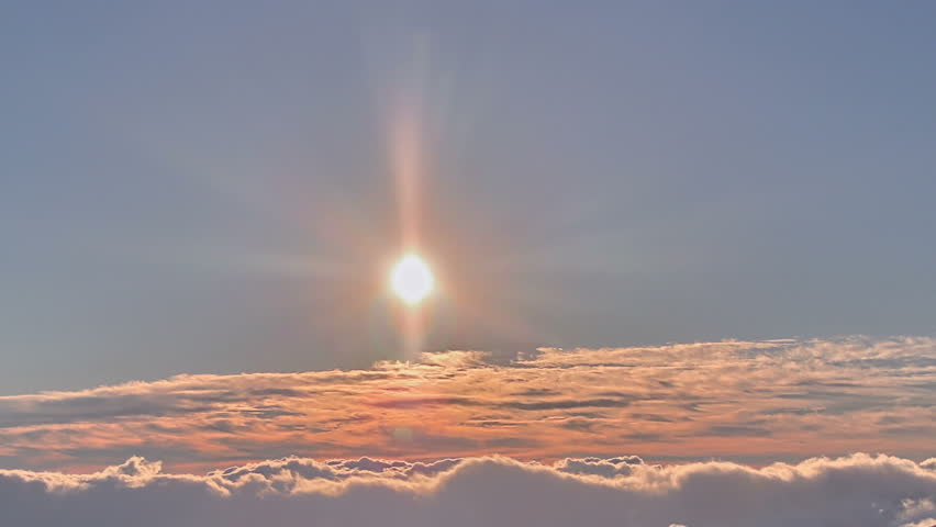 Brilliant summit dawn above flowing cloud waves, red sun disk time lapse in HDR