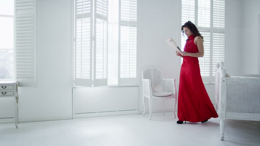 Beautiful woman in red evening gown returns home to her elegant white apartment and takes off her shoes as she reads the morning newspaper.