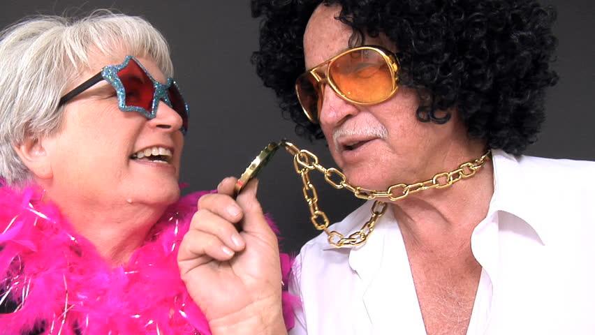 Senior couple in costumes singing and having fun
