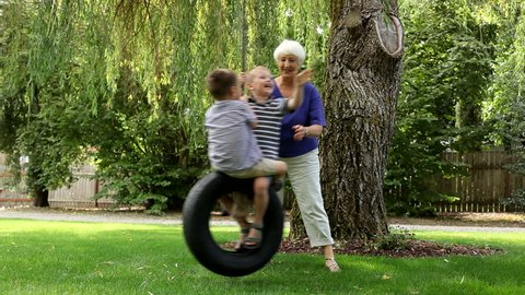 Woman pushing grandchildren on swing