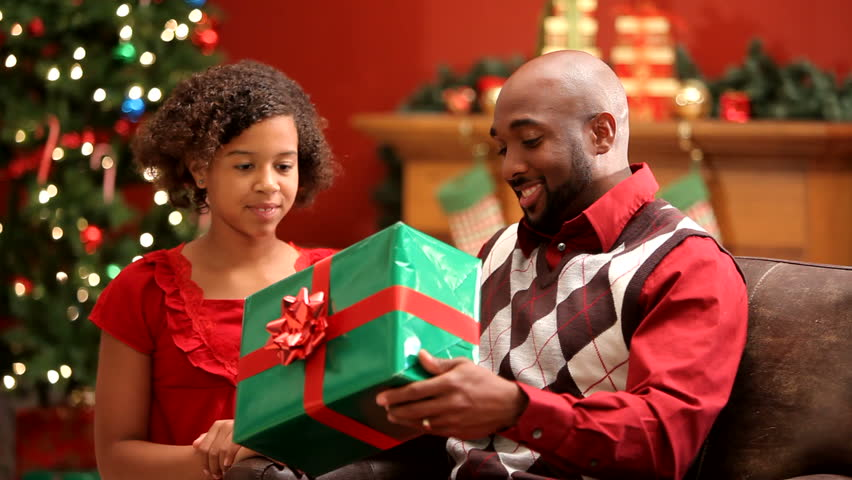 Father and daughter exchanging gifts at Christmas