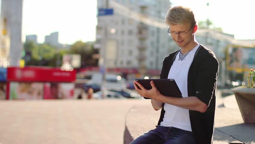 Smiling man reading electronic pad tablet pc, looking at camera