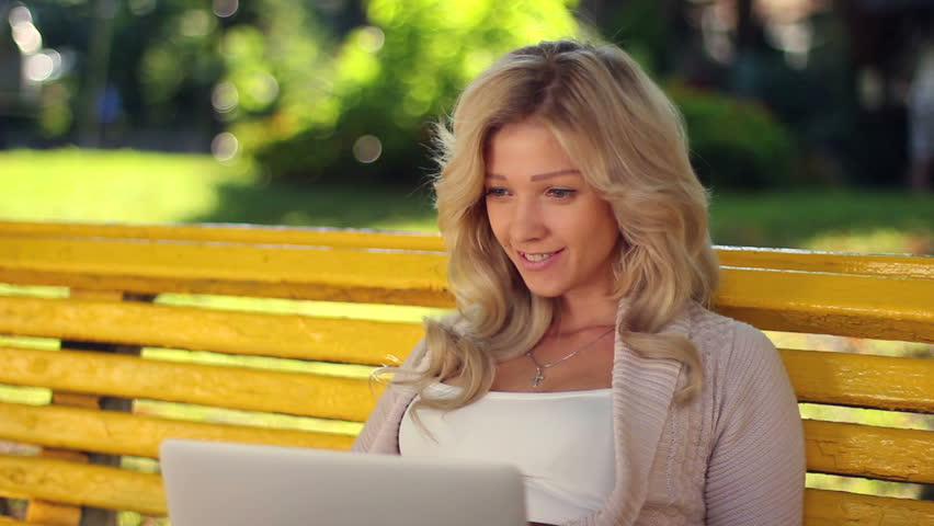 Female smiles laughs reads laptop in park, girl giggles on bench