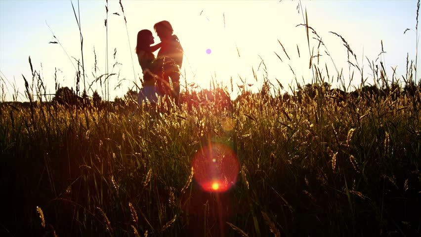 A silhouetted couple hug, kiss and then walk in a wide open golden field at sunset  #4579328