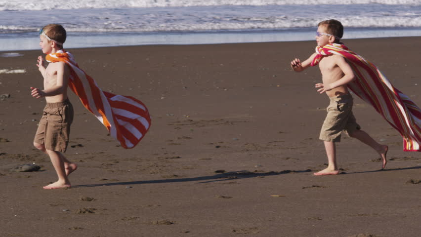 Young boys running at beach with superhero costumes
