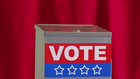 Hand putting vote into ballot box