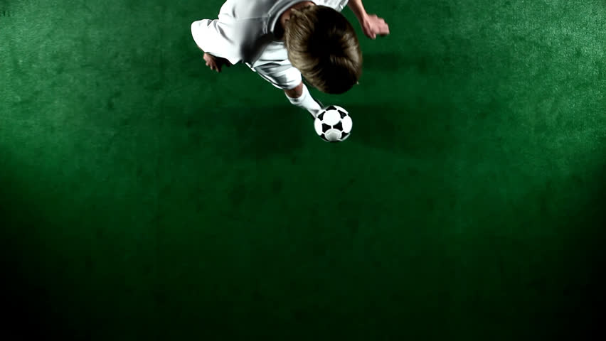 A soccer, or football, player that is dramatically and artistically lit, on an artificial field pitch on a black background, juggles the ball. As seen from above looking down. | Shutterstock HD Video #4604918