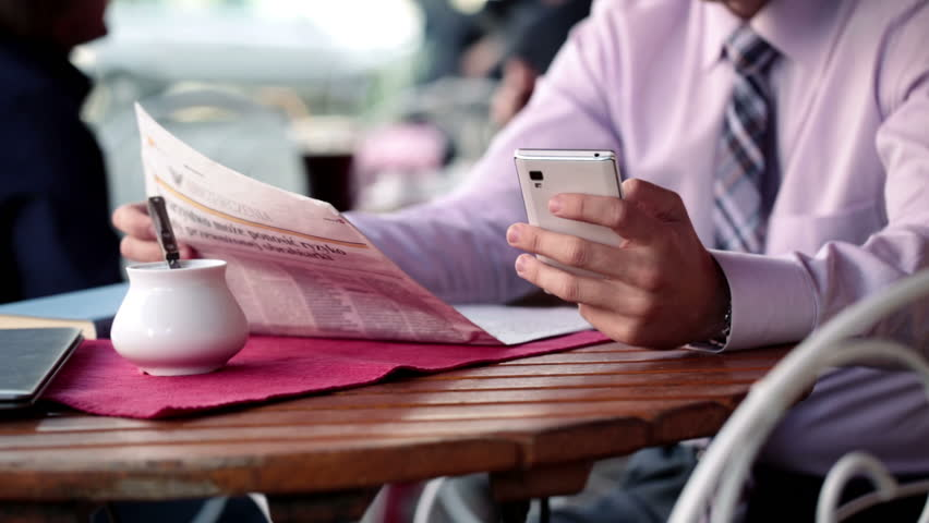 Young businessman with smartphone and newspaper in cafe