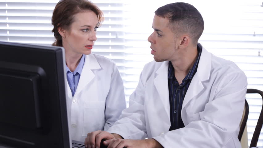 Two doctors, technicians, or scientists working together on a computer.