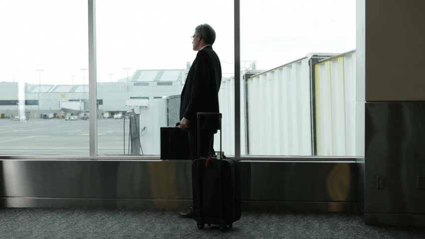 Mature business man at airport waits for airplane