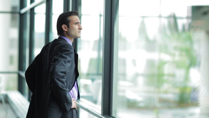 A businessman looks out the window in a contemplative way. Medium shot | Shutterstock HD Video #4631570