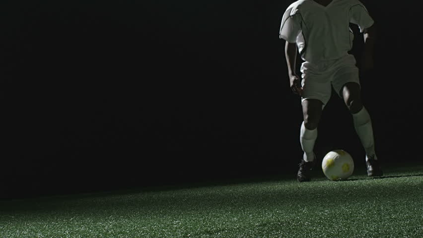 Close up of a soccer player jumping over a sliding defender