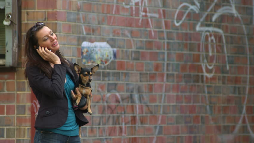 A woman holds her dog in her arm and talks on her cell phone in front of a cool city wall with graffiti