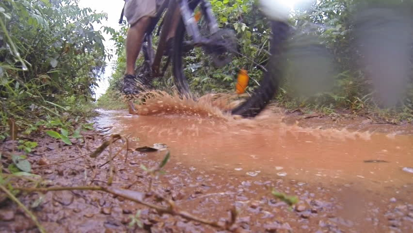 Mountain bike passing in a muddy trail with water splash. Recorded at slow motion 120fps