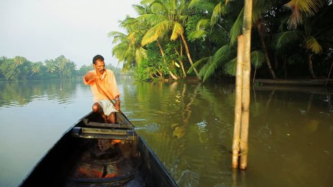 India - January 2011: Traditional canoeing transit by a local man in a river near Alleppey, Kerala, India in January, 2011