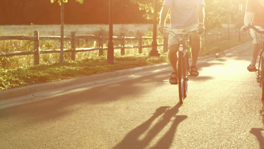 An older couple rides bikes down the street at sunset in slow motion as the camera follows them. With lens flare