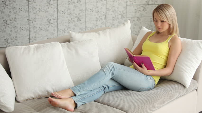 Attractive girl relaxing on sofa reading book closing it and smiling