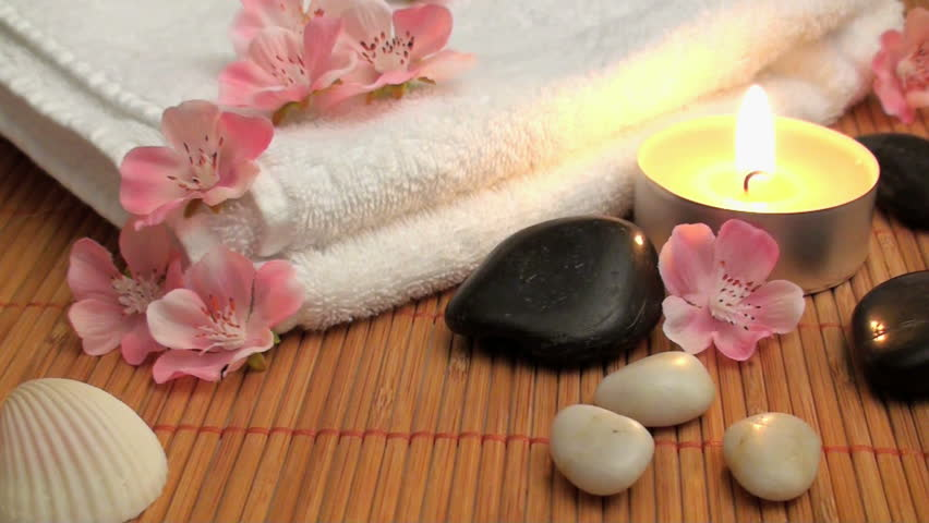 wellness time with candle, stones and blossoms