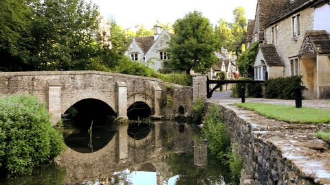 Scenic view of a family of ducks passing under a stone footbridge in the peaceful rural  town of Castle Combe Village in Wiltshire, United Kingdom