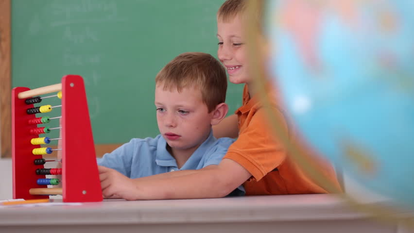 Two boys at school counting with abacus