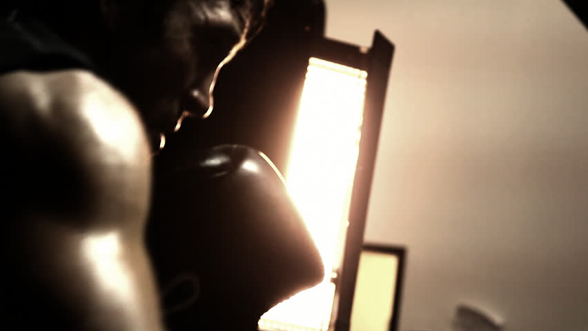 Boxer works on his striking by hitting a punching bag. Close up shot.