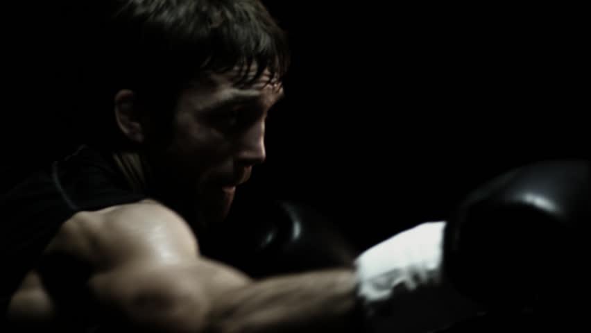 Strong athlete hits a punching bag. Medium shot.
