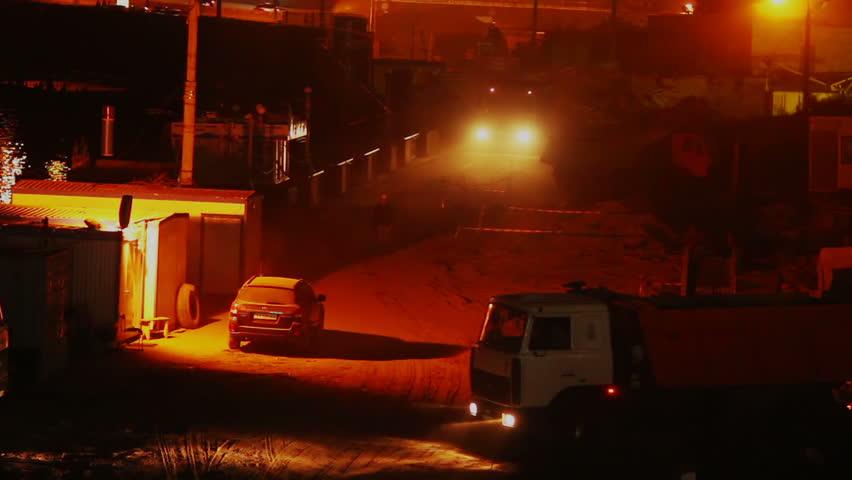Construction yard night shift, trucks work driving, building