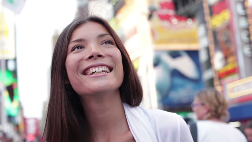 Happy woman tourist in New York City, Manhattan, Times Square. Girl traveler looking around joyful and happy smiling at city lights in downtown New York. Multiethnic Asian Caucasian woman in her 20s.