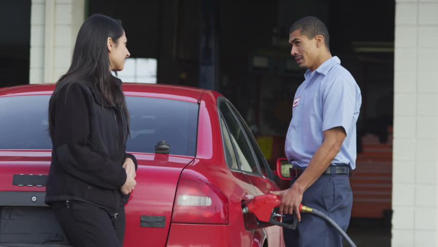 Service station worker talks with customer