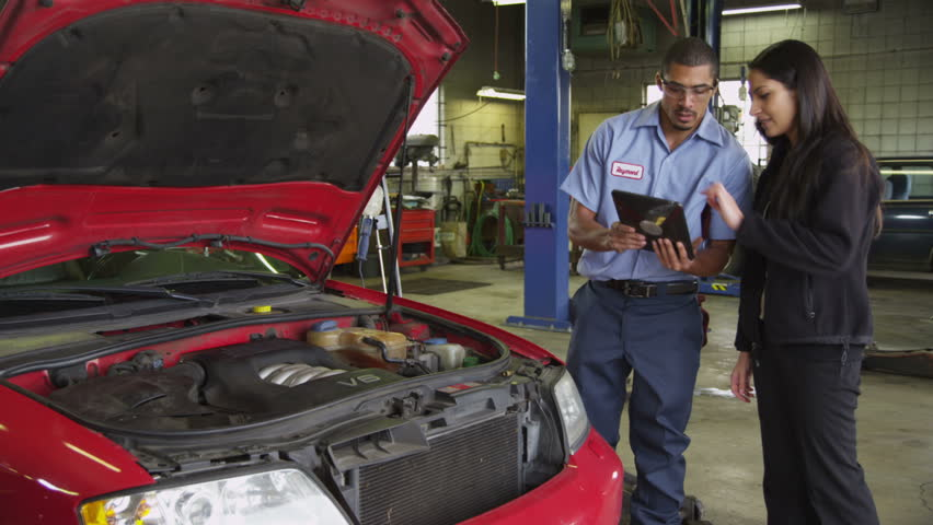 Mechanic in auto shop helps customer with digital tablet
