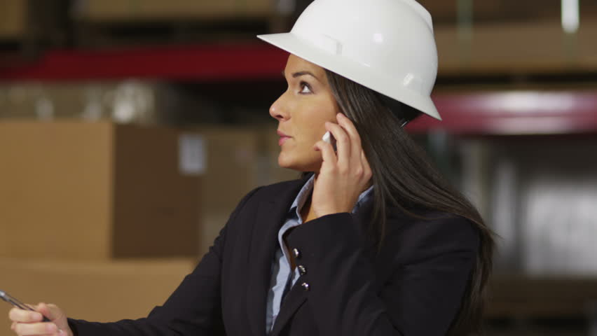 Business woman in warehouse talking on cell phone