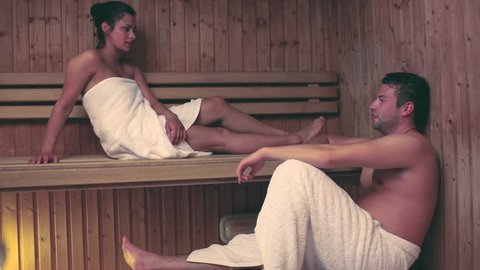Couple relaxing and speaking together in a sauna at the hotel spa
